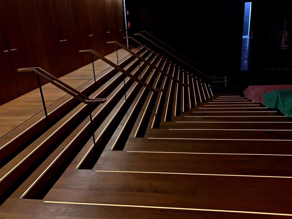 Stufenbeleuchtung in einem Theater. Die einzelnen Treppenkanten sind durch eckige Leuchten beleuchtet. Die Beleuchtung auf den lange Treppen leuchtet blendfrei ohne sichtbare LED Punkte.