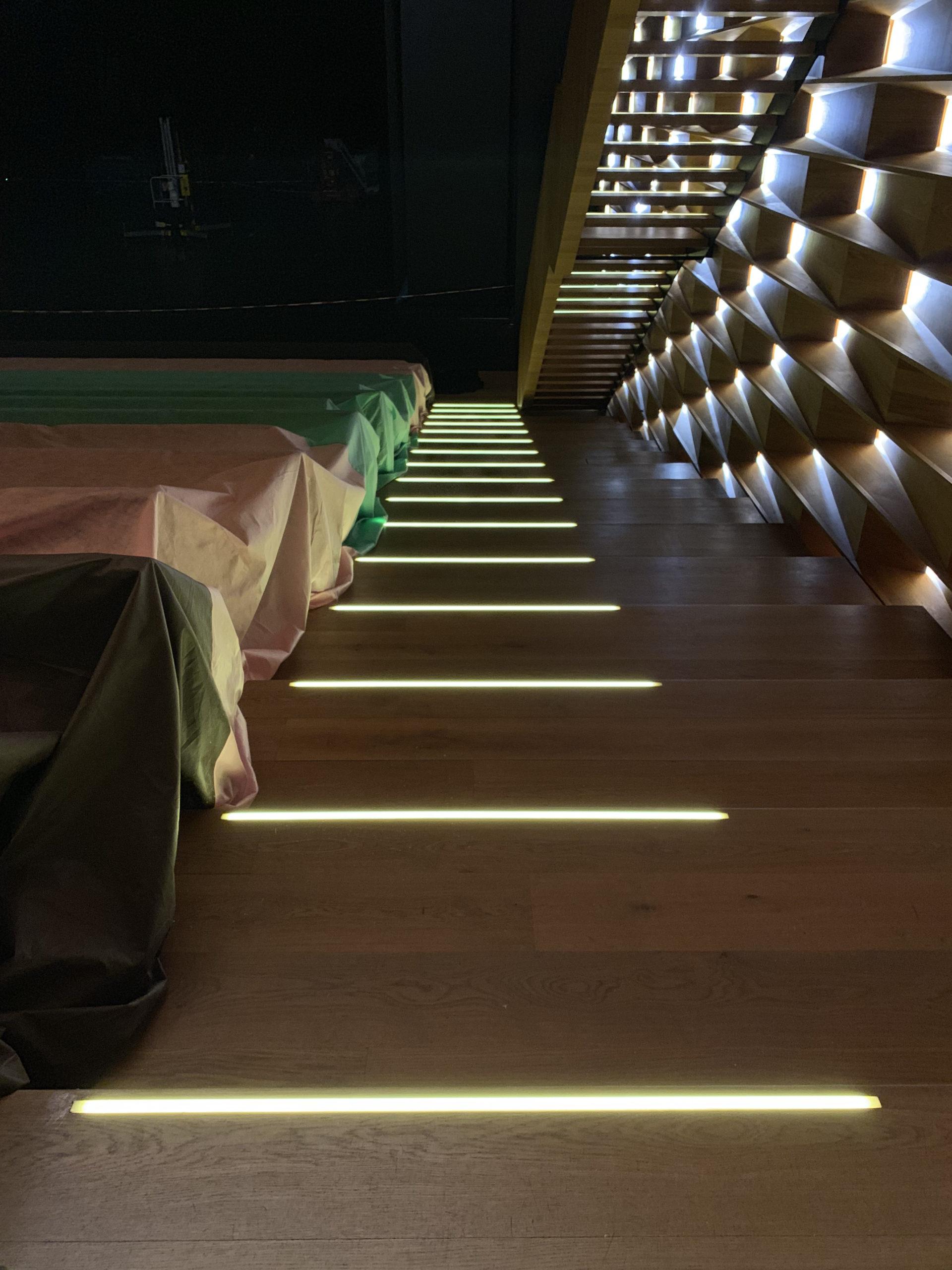 Holzstufen mit eckigen Einbauleuchten. Seitlich sind Leuchten für einen Wandeinbau zu sehen.