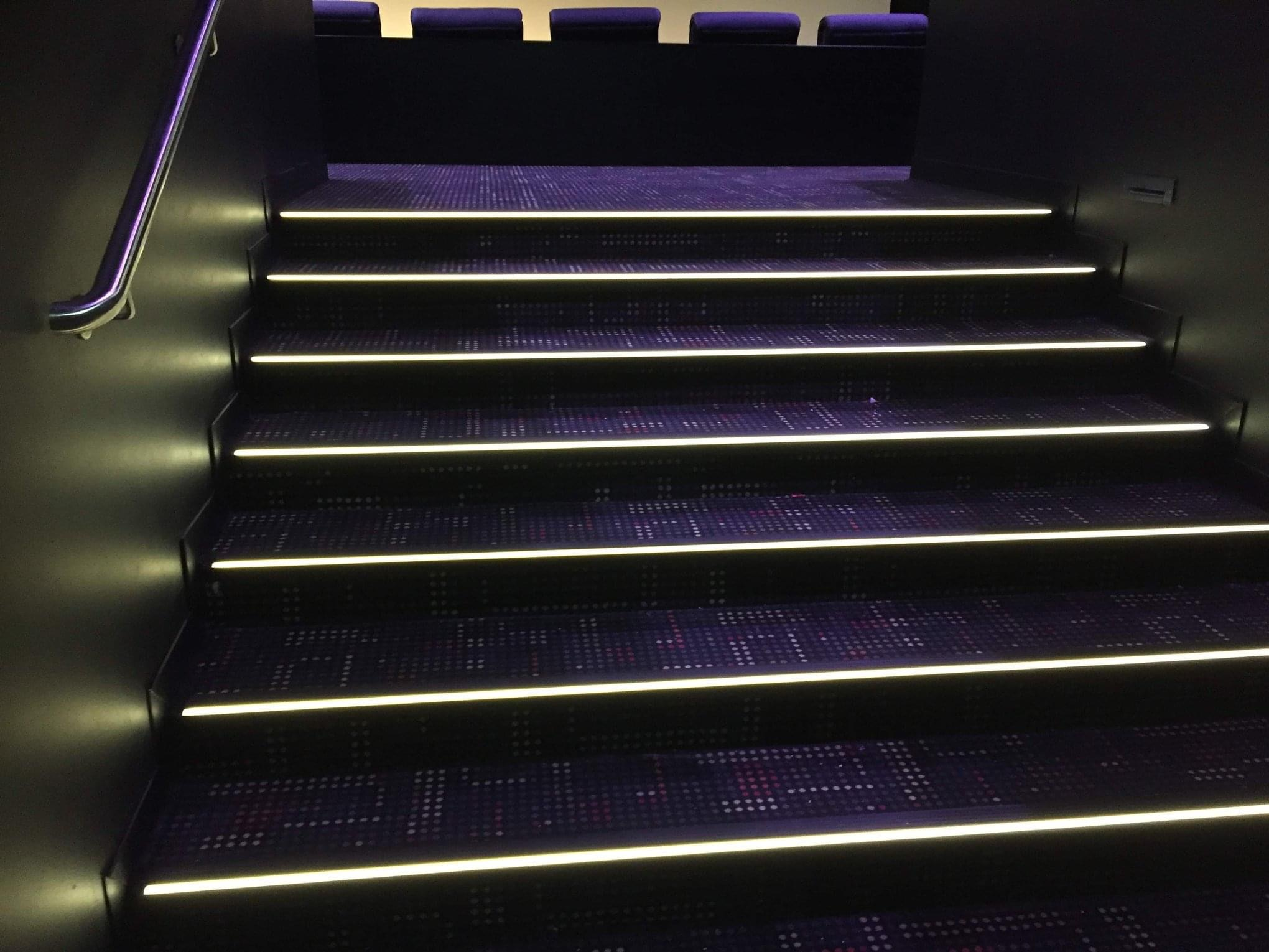 Eingangsbereich eines Auditoriums mit Leuchtenden Treppenstufen. Die komplette Kante leuchtet leicht abgedunkelt in weiß